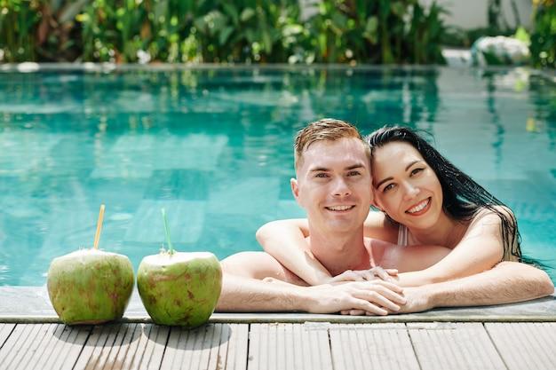 Hermosa joven pareja abrazándose apoyado en el borde de la piscina junto a cócteles de coco y sonriendo al frente