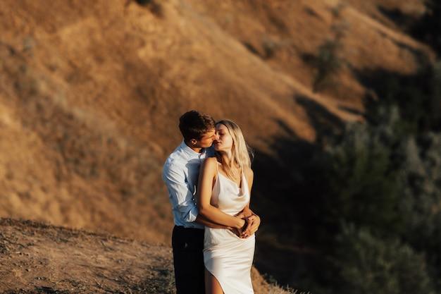 Hermosa joven pareja abrazándose en una colina. concepto de día de la familia.