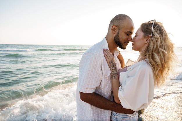 Hermosa joven pareja abrazándose en la playa por el agua