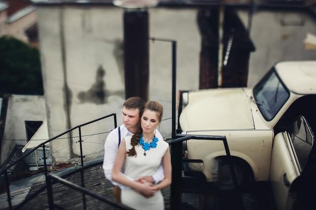 Hermosa joven pareja abrazos en escaleras de caracol en el techo