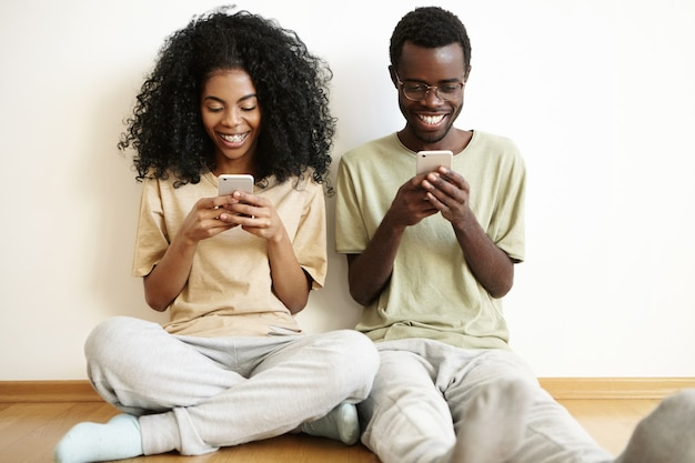 Hermosa joven pareja africana disfrutando de la comunicación en línea en casa, sentada en el piso, usando aparatos electrónicos