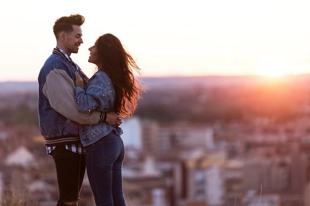 Hermosa joven pareja en el amor de pie en la azotea de un edificio en la puesta del sol.