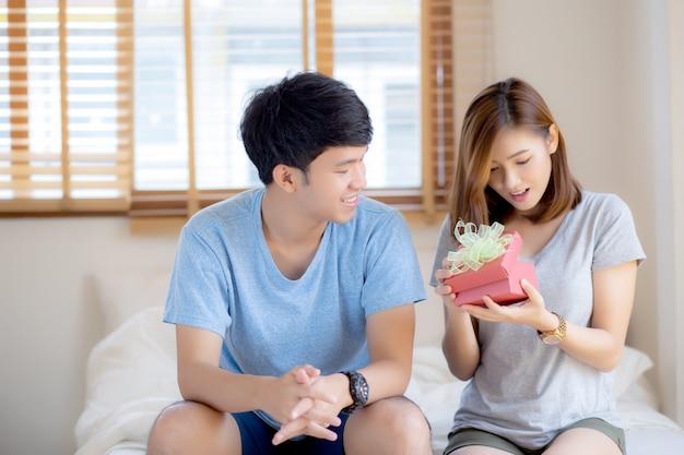 Hermosa joven pareja asiática en caja de regalo sorpresa de amor