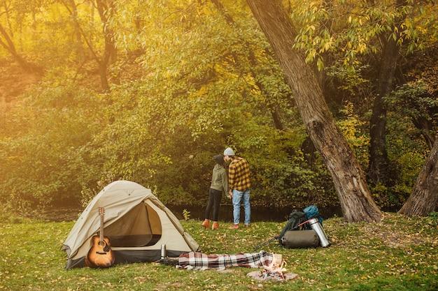 Hermosa joven pareja besándose en el campamento
