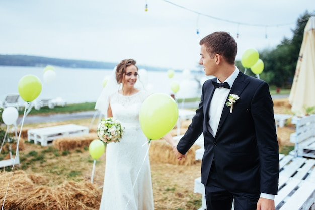 Hermosa joven pareja besándose, novia rubia con flor