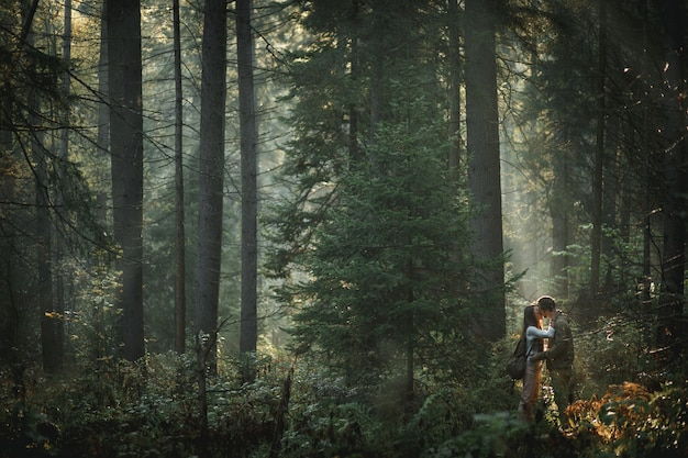 Hermosa joven pareja beso al aire libre en el bosque, amor verdadero y pasión