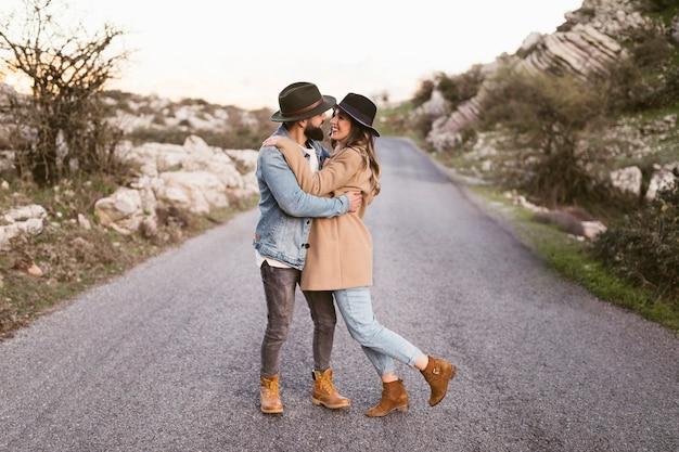 Hermosa joven pareja caminando por una carretera
