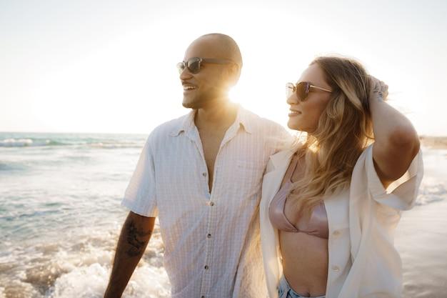 Hermosa joven pareja caminando en la playa cerca del mar