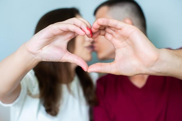 Hermosa joven pareja en casa haciendo un signo de corazón con las manos, sonriendo y besando. celebración del día de san valentín, amor.