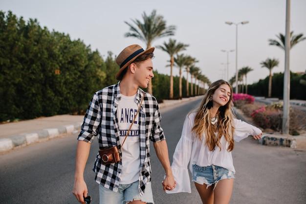 Hermosa joven pareja en una cita romántica al aire libre disfruta de la libertad y las cálidas noches de verano en el sur de la ciudad. chico en camisa a cuadros de moda y chica en blusa blanca vintage caminando por la carretera cogidos de la mano