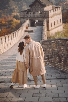 Hermosa joven pareja cogidos de la mano y mostrando afecto en la gran muralla de china.