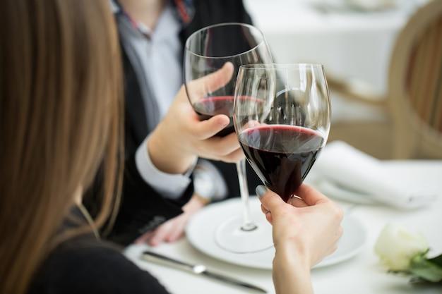 Hermosa joven pareja con copas de vino tinto en un restaurante de lujo