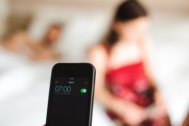 Hermosa joven pareja despertando con despertador móvil