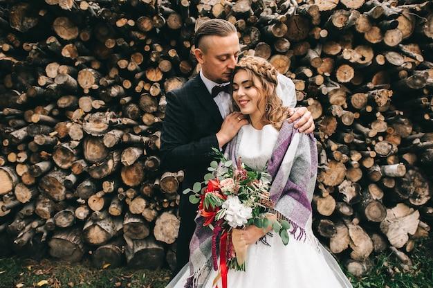 Hermosa joven pareja en el día de la boda en la pared de fondo con troncos de madera