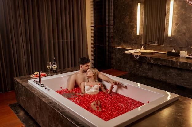 Hermosa joven pareja disfrutando de un baño con pétalos de rosa