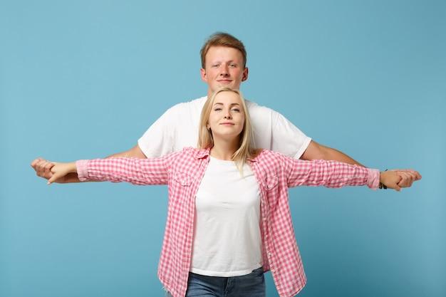Hermosa joven pareja dos amigos chico chica en blanco rosa diseño en blanco vacío camiseta posando