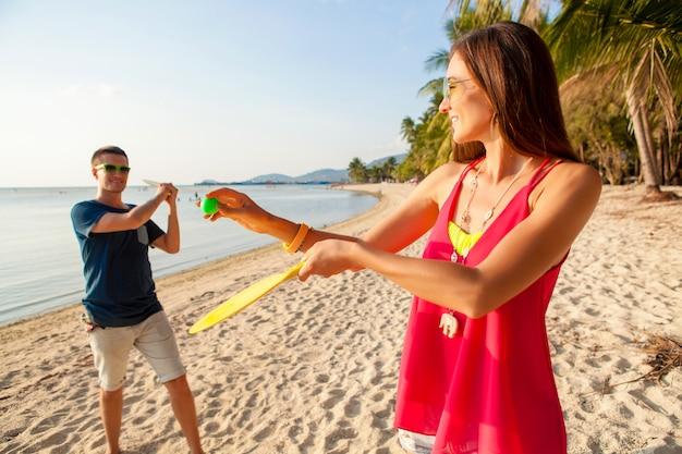 Hermosa joven pareja de enamorados jugando al ping pong en la playa tropical, divirtiéndose, vacaciones de verano, activo, sonriente, divertido, positivo