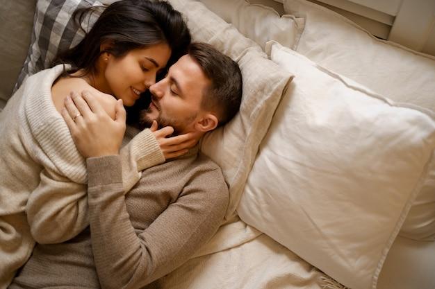 Hermosa joven pareja feliz descansando en la cama y sonriendo, abrazando