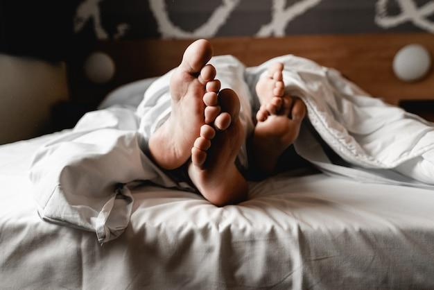 Hermosa joven pareja feliz o familia despertando juntos en la cama