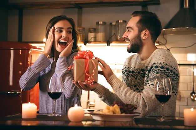 Hermosa joven pareja feliz pasar una velada romántica juntos en casa, bebiendo vino tinto, hombre dando un regalo