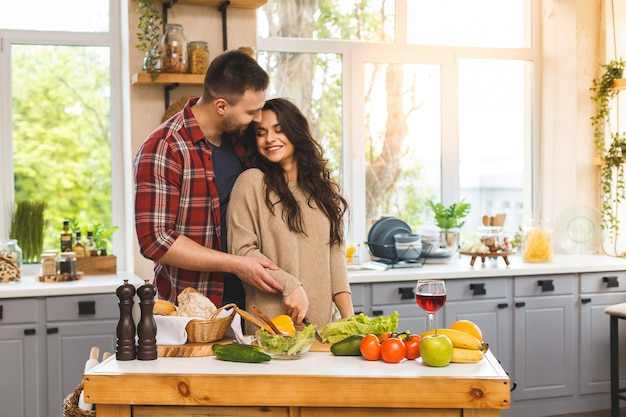 Hermosa joven pareja feliz sonriente está hablando y sonriendo mientras cocina alimentos saludables en la cocina en casa.