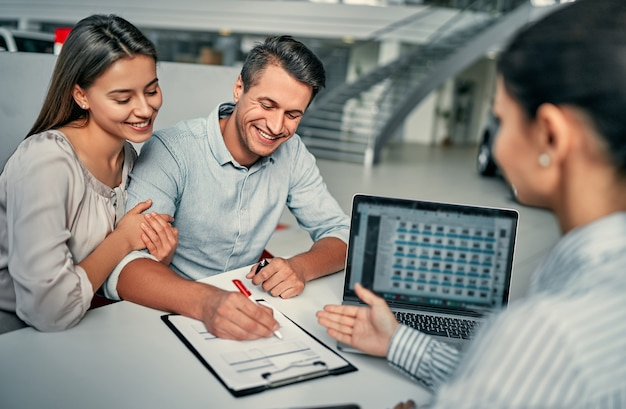 Hermosa joven pareja firma documentos en la sala de exposición del concesionario. compra y alquiler de coches.