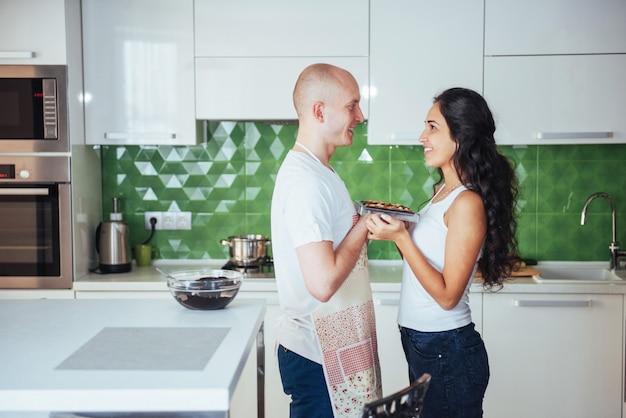 Hermosa joven pareja graficaba miling a la cámara mientras cocinaba en la cocina en casa.