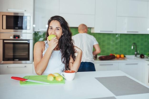Hermosa joven pareja graficaba sonriendo mientras cocinaba en la cocina en casa.