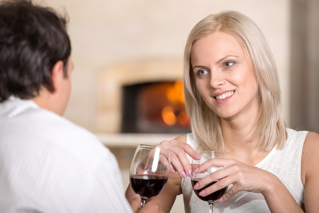 Hermosa joven pareja está hablando y beber vino.