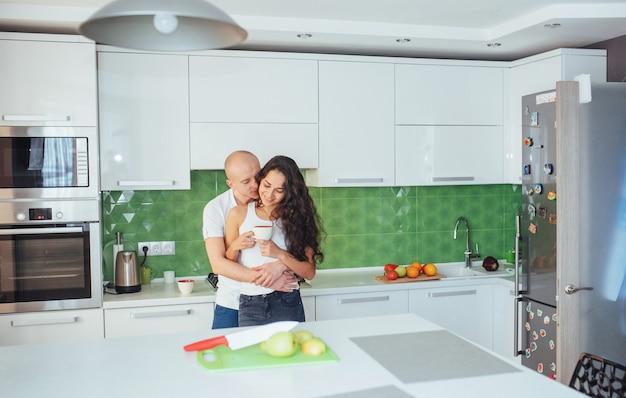 Hermosa joven pareja está hablando, mirando a cámara y sonriendo mientras se cocina en la cocina.
