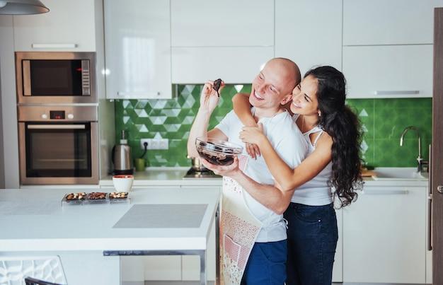Hermosa joven pareja hablando, mirando y sonriendo mientras se cocina en la cocina.