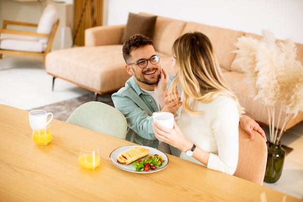 Hermosa joven pareja hablando y sonriendo mientras come saludable en casa.