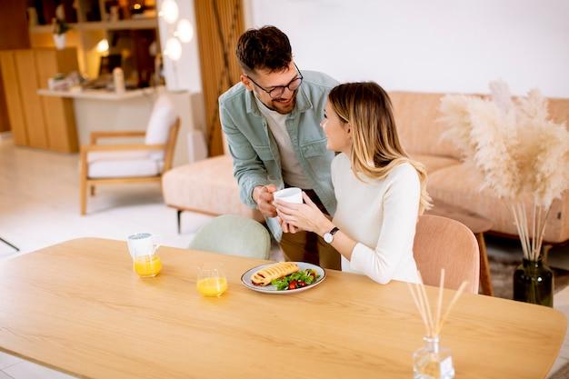 Hermosa joven pareja hablando y sonriendo mientras come sano en casa.