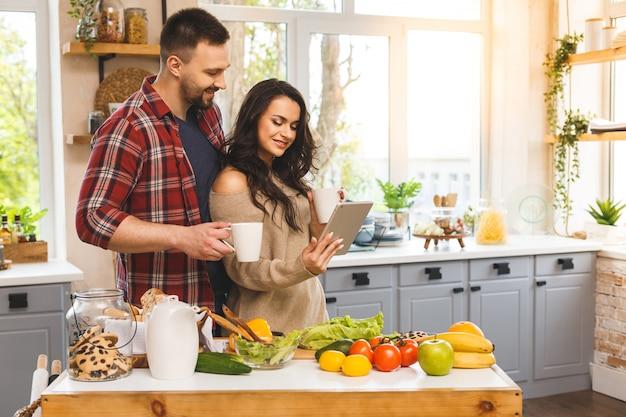 Hermosa joven pareja está hablando, sonriendo mientras come té o café y bebe en la cocina en casa. usando tableta.