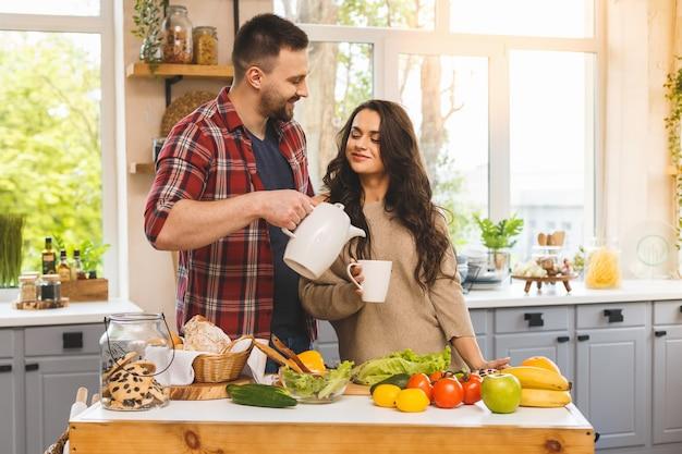 Hermosa joven pareja está hablando, sonriendo mientras come té o café y bebe en la cocina en casa