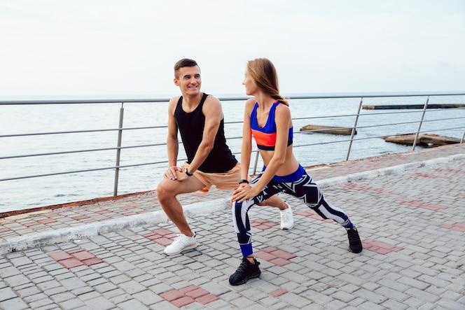 Hermosa joven pareja haciendo ejercicios de deportes, mirando el uno al otro, estirando el cuerpo