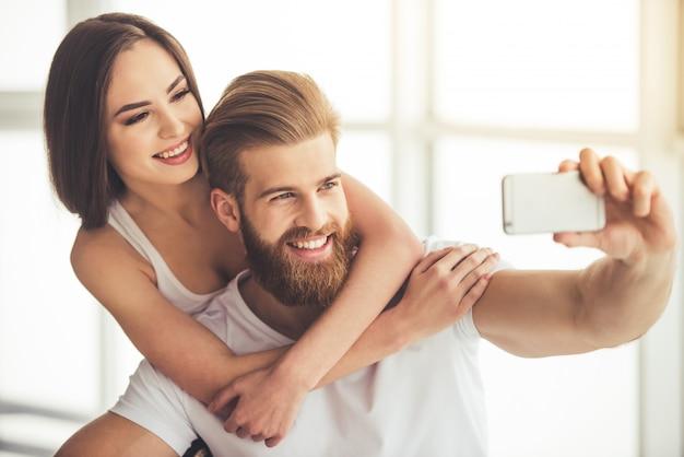 Hermosa joven pareja está haciendo selfie usando un teléfono inteligente.