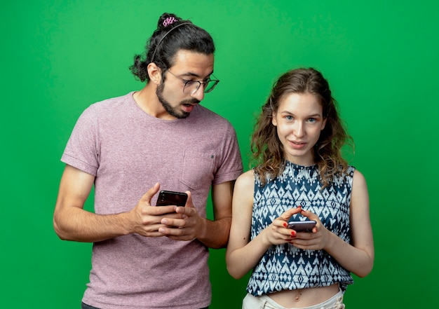 Hermosa joven pareja hombre y mujer, hombre espiando y mirando el teléfono celular de su novia sobre la pared verde
