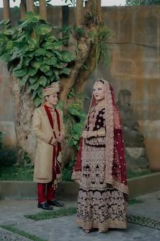 Hermosa joven pareja india musulmana con lujoso atuendo típico