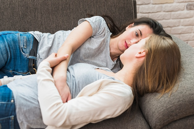 Hermosa joven pareja lesbiana tumbada en el sofá mirando el uno al otro