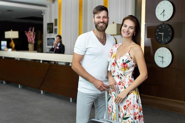 Hermosa joven pareja marido y mujer con maleta en la recepción del hotel.