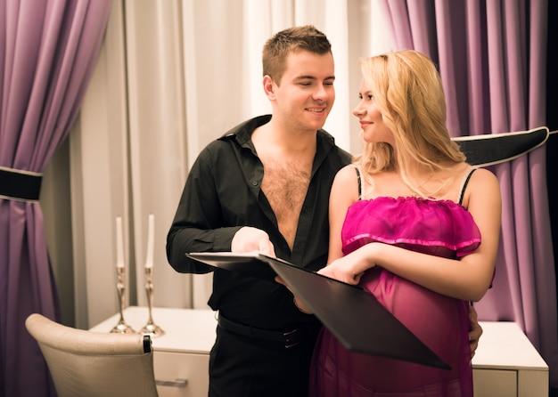 Hermosa joven pareja marido y mujer mirando catálogo de muebles eligiendo una cama para su futuro bebé.