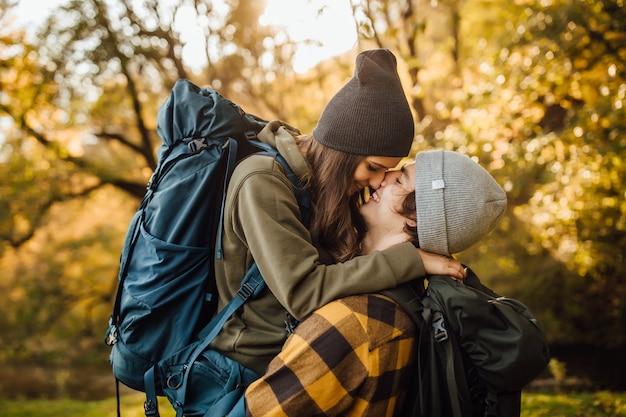 Hermosa joven pareja con mochila de senderismo besándose en el bosque