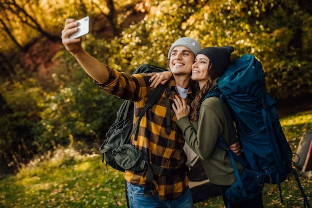 Hermosa joven pareja con mochilas de senderismo hacen selfie durante el trekking