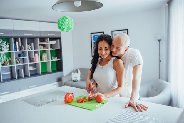 Hermosa joven pareja muele verduras juntos en la cocina.