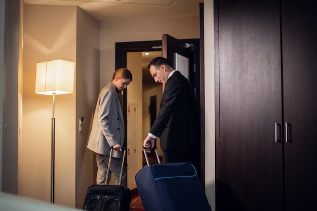 Una hermosa joven pareja de negocios saliendo de su habitación de hotel con las maletas
