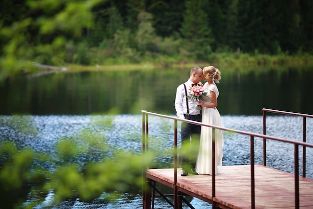 Hermosa joven pareja, novia y el novio posando en el fondo del lago. el novio y la novia en el muelle.