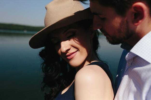 Hermosa joven pareja pasa tiempo en el muelle de madera en el lago