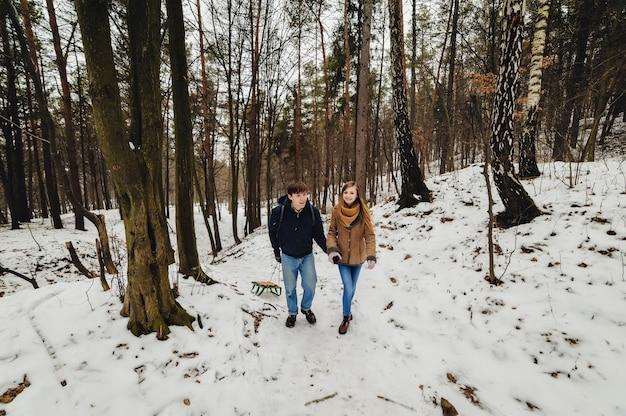 Hermosa joven pareja en un paseo tirando del trineo, día de invierno. felices vacaciones. feliz navidad y próspero año nuevo concepto.