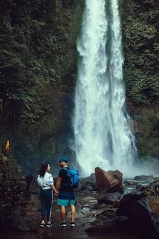 Hermosa joven pareja posando en la cascada, viajeros, excursionistas, mochilas